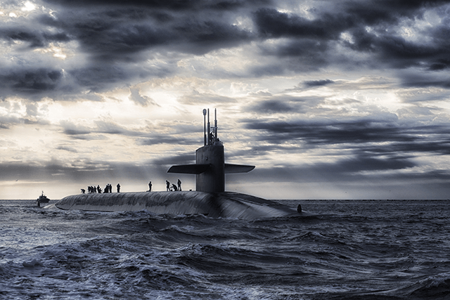 Submarine on top of ocean with sailors on deck
